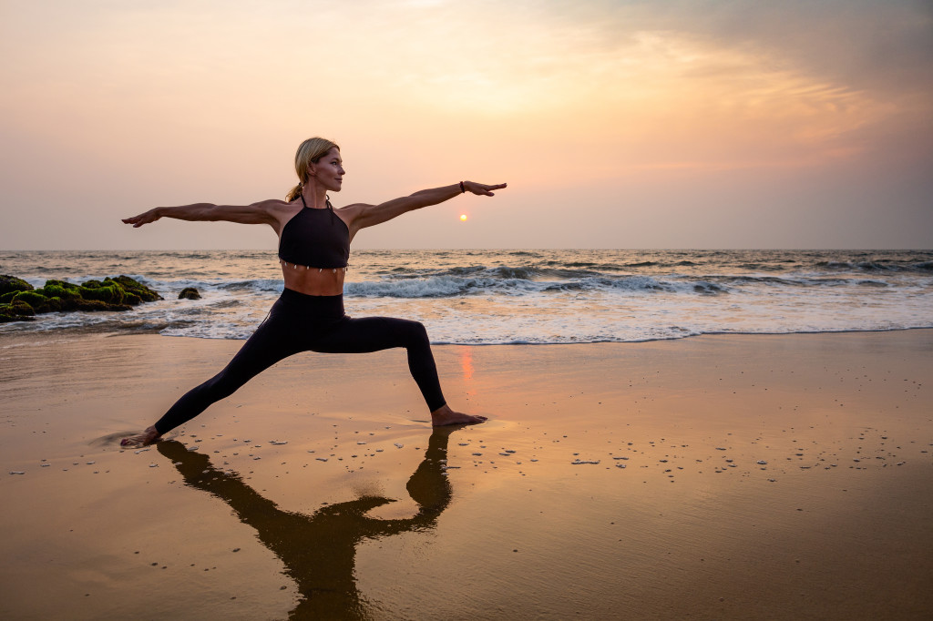 Middle age woman in black doing yoga on sand beach in India